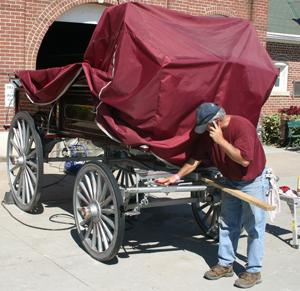 David Brown, Pearl City, Ill., cleans his hitch wagon for the draft horse hitch show. This style of wagon was once used for delivery of various goods. Brown's family, owners of Plum Creek Farms, have been competing in state fairs across the nation for 10 years.