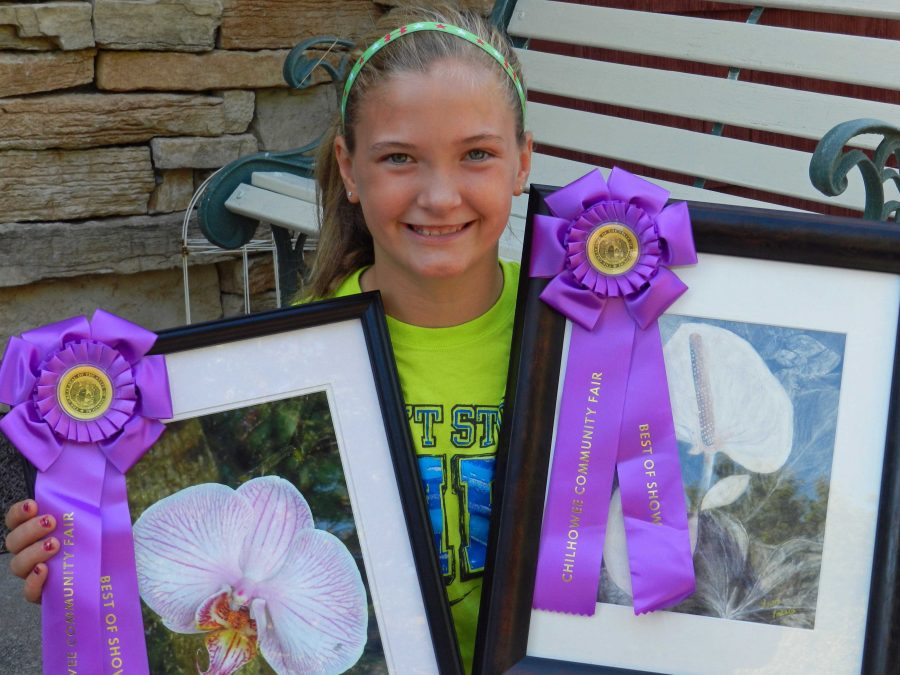 Laura+Lockard%2C+a+sixth-grade+student+at+Warrensburg+Middle+School%2C+displays+her+Best+of+Show+awards+from+the+Chilhowee+Fall+Fair+Fine+Arts+Competition.+She+earned+Best+of+Show+in+both+Youth+Under+17+Photography+and+Youth+Under+17+Art.+A+trip+to+Powell+Gardens+provided+the+subject+matter+for+her+charcoal+drawing+and+photo.