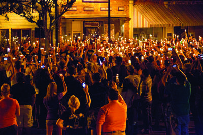 In a moment of unity, the Warrensburg and UCM communities gather on Holden Street with candles lit in remembrance of Blaine Whitworth, UCM graduate and bar owner. (Photo by ANDREW MATHER, Photo Editor, Muleskinner)