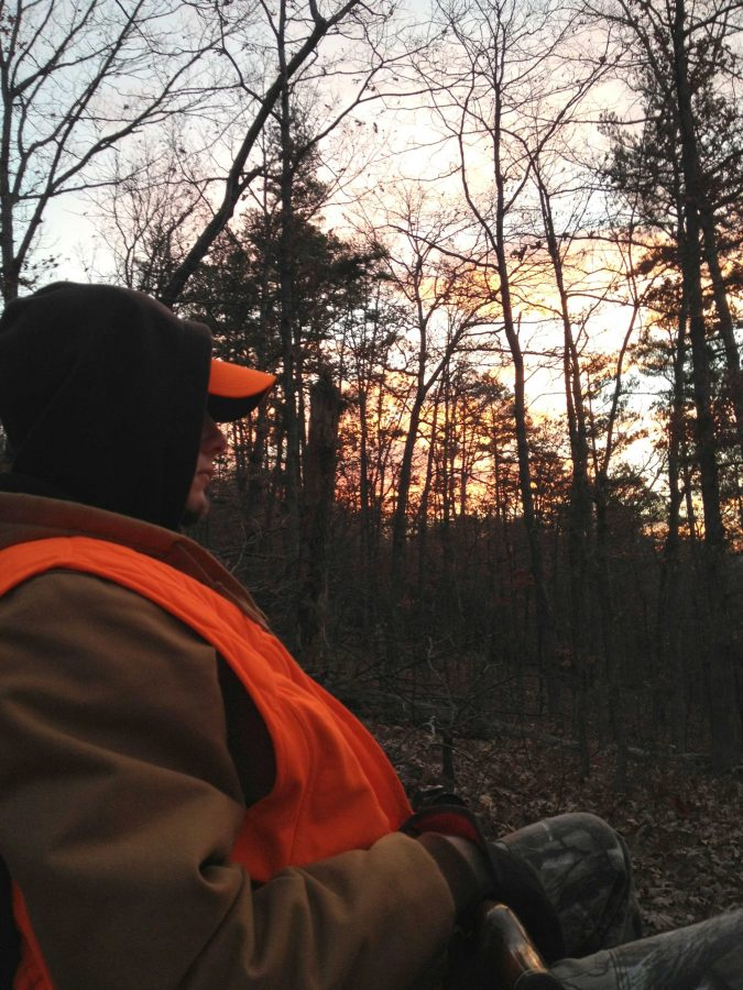 (Photo by Katie Douglas) Ian Rowland sits with a gun across his lap, ready for a deer to draw near.