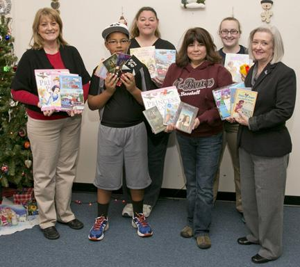 (Courtesy photo) Mary Clevenger, left, outreach coordinator for KMOS-TV, and Rosemary Olas, right, UCM's interim director of broadcasting services, presented more nearly 900 children's books to Johnson County Community Christmas Angel Tree volunteers, from left, Xavier Hardin, Jennifer Hardin, Valentina Kelleher and Cassie Williams.