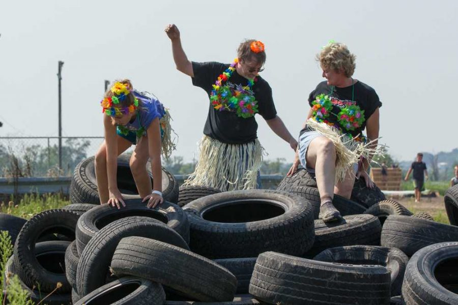 This family, dressed in luau attire complete with grass skirts, coconut bras, and vibrantly colored flower leis, climb over a pile of tires on their way to the finish line.