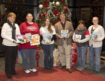 Mary Clevenger, left, outreach coordinator for KMOS-TV, and Mark Pearce, third from right, coordinator of corporate and community support, presented children's books to Johnson County Community Christmas Angel Tree volunteers, from left, Jennifer Hardin, Wendy Wood, Valentina Kelleher and Cassie Williams.