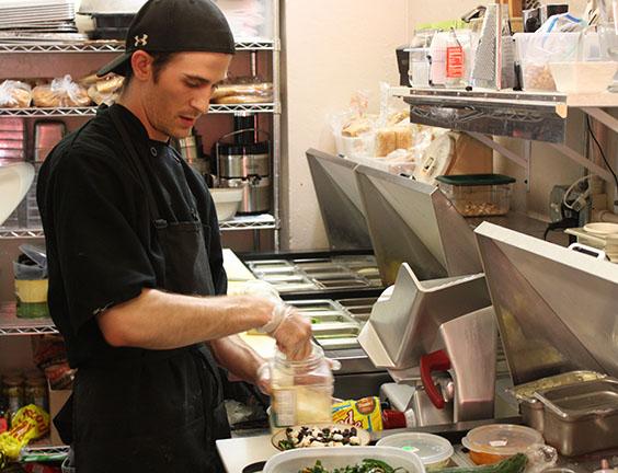 Photo by Kevin Lyon/digitalBURG Ian Zoellers prepares a kale salad at Cafe Blackadder.