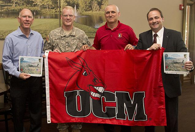 University+of+Central+Missouri+alumnus+Patrick+Stueve%2C+second+from+left%2C+presents+one+of+two+UCM+flags+with+the+Mule+head+logo+to+President+Charles+Ambrose%2C+left.+Ambrose+had+the+flags+sent+to+Stueve+in+Afghanistan.++Joining+Stueve+and+Ambrose+for+the+presentation+were+Jeff+Huffman%2C+third+from+left%2C+director+of+Military+and+Veteran+Services%2C+and+Tony+Monetti%2C+assistant+dean+of+aviation+and+executive+director+of+the+Max+B.+Swisher+Skyhaven+Airport.