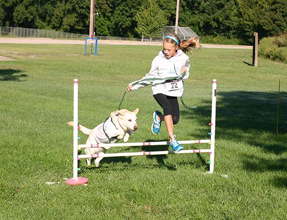 Kambree Peterson of Warrensburg leads her dog Koda over a jump as part of an obstacle course during Bark in the Park on Saturday September 13th.