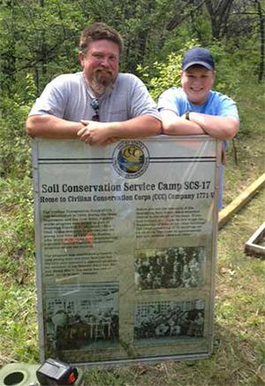 Photo courtesy of UCM University Relations Trent Courtwright, right, and his father, Kevin, installed signage at the site of the former Civilian Conservation Corps camp at Pertle Springs as part of Trent's Eagle Scout community project.