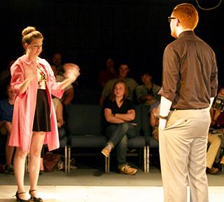 """From left, Sarah Bronson as young woman and Caleb Gazaway as young man, stand far from each other Friday night in the Black Box Theatre, wondering where their first date is going to lead them as part of the """"Coax"""" play for the Studio One-Act series."""