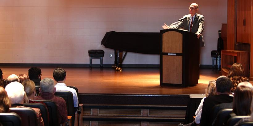 President Chuck Ambrose speaks to the crowd Thursday, Oct. 26, about budget cuts in the Utt music building at the State of the University address.