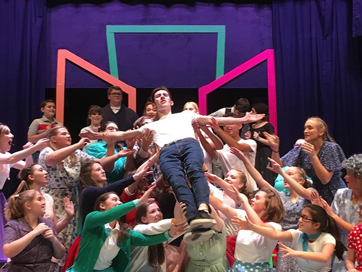 An adoring throng of Conrad Birdie fans lift the star as he sings to the town of Sweet Apple, Ohio.  Conrad Birdie is portrayed by sophomore Kaden Callahan.