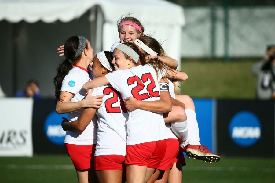 PHOTO BY ANDREW MATHER / PHOTOGRAPHER Megan Woolley (pink Headband) is embraced by her teammates after scoring the first goal. The Jens would beat Mercy College 3-0 Thursday before going on to take the national  championship against Carson-Newman Saturday afternoon.