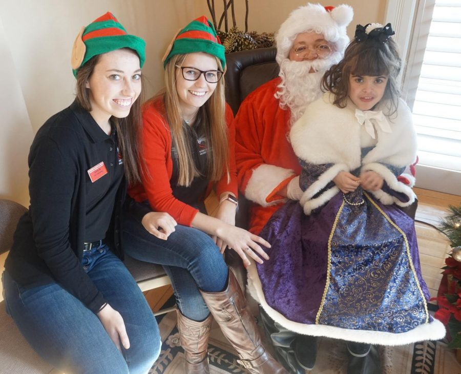 Photos by Naporsha: Williams Santa and his elves pose with the child of a UCM faculty member during the Holiday Open House. From left: Julianne Kufmann, junior, Courtney Abt, senior, Santa, and Annika Brunsvold.