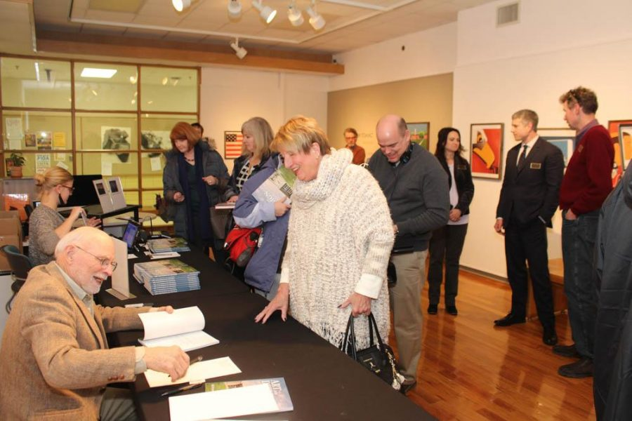 """Rich Monson, an author of the book """"Art and Design At Central,"""" signs a copy of the book as attendees mingle with each other and former art and design department faculty at the book signing Thursday, Feb. 1, in the Art Center."""