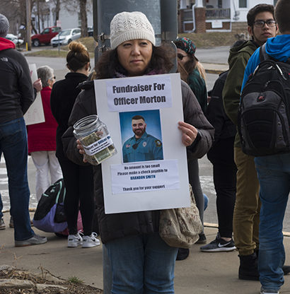 PHOTO BY Colin OBrien / Photographer A woman honors Clinton Police Officer Christopher Morton by fundraisingTuesday afternoon in competition with a Westboro Baptist Church protest that occurred at the intersection of Maguire and Clark streets Tuesday, March 12.