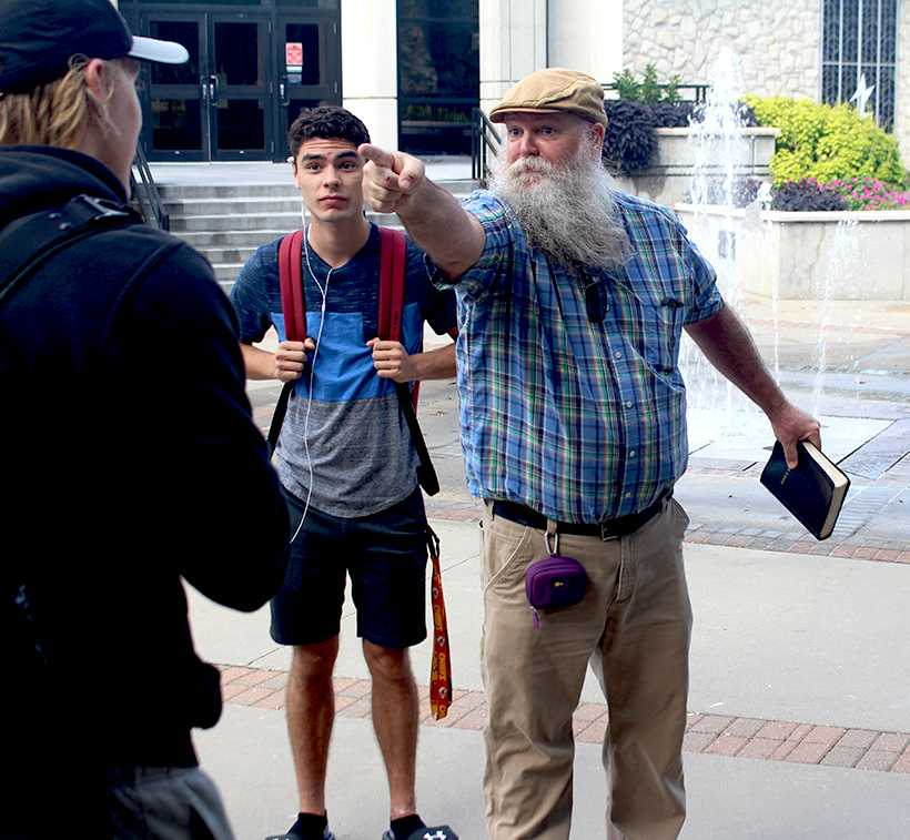 Jeff Mullen has an exchange with a passing student Tuesday in front of the east entrance of the Elliott Student Union. Mullen and his wife, Pam, were on campus to warn the campus community about the wages of its sin and to warn about the perils of hell.