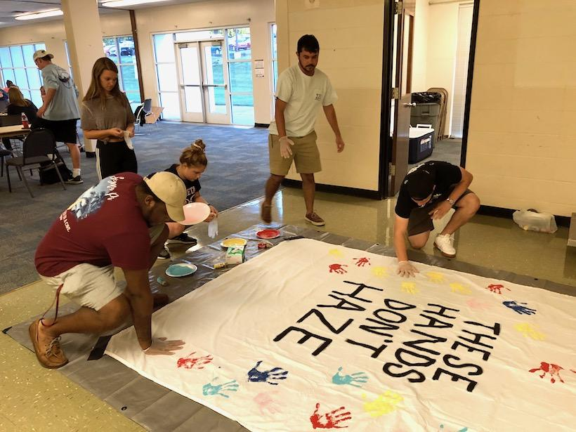 Sorority and fraternity members gather to place their paint-coated handprint on an anti-hazing banner during Trivia Night Wednesday, Sept. 19. (Photo by Madeline Turner, for the Muleskinner)