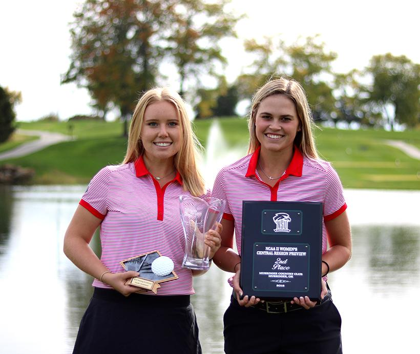 Junior Olivia Sobaski (left) and freshman Rosie Klausner (right) show off the Jennies hardware from the fall 2018 season. (Photo by Molly Burnam/Photo Editor)