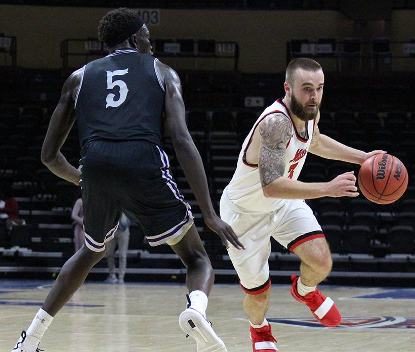 Junior Blake Spellman dribbles past a defender in the Mules overtime loss to Sioux Falls in Kansas City. Spellman is averaging 12.4 points per game and has scored in double figures in all but one game this season. (Photo by Jason Brown/Sports Editor)