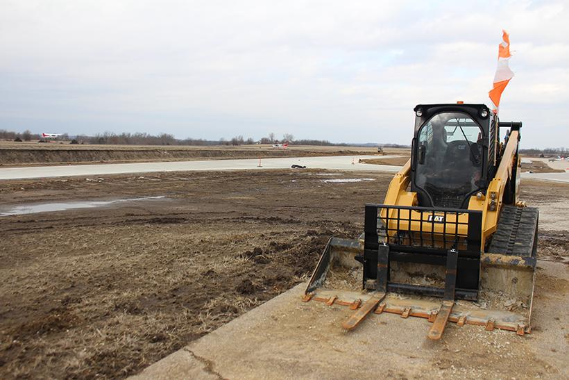 A skid-steer loader is parked by the muddy construction site at Max B. Swisher Skyhaven Airport, where the $7 million runway and taxiway resurfacing project is underway. (Photo by Garrett Fuller, senior writer.)
