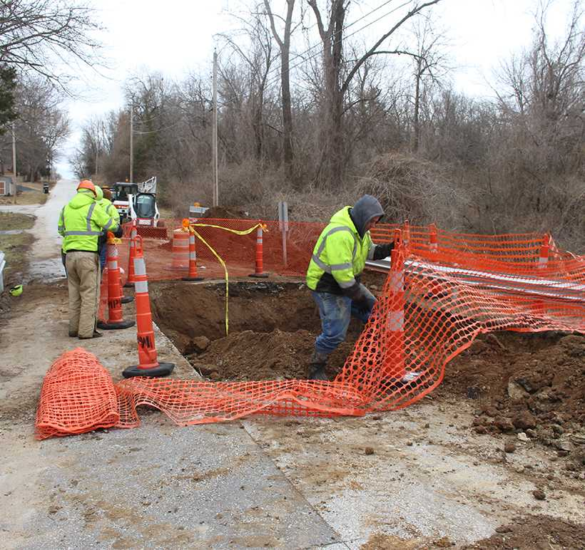 Workers from the Warrensburg Street Department set up netting around a sinkhole that formed on South Main Street. (Photo by Jason Brown/Managing Editor)