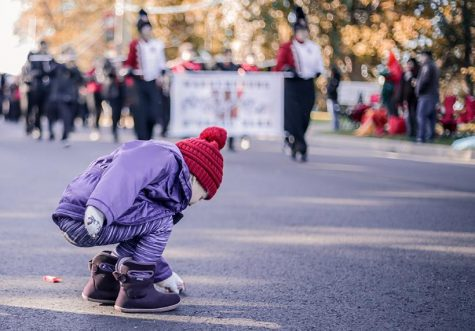 A parade spectator takes advantage of a break in the action to go after some candy at the 2019 Homecoming parade. (Photo by Alexis Dyser)
