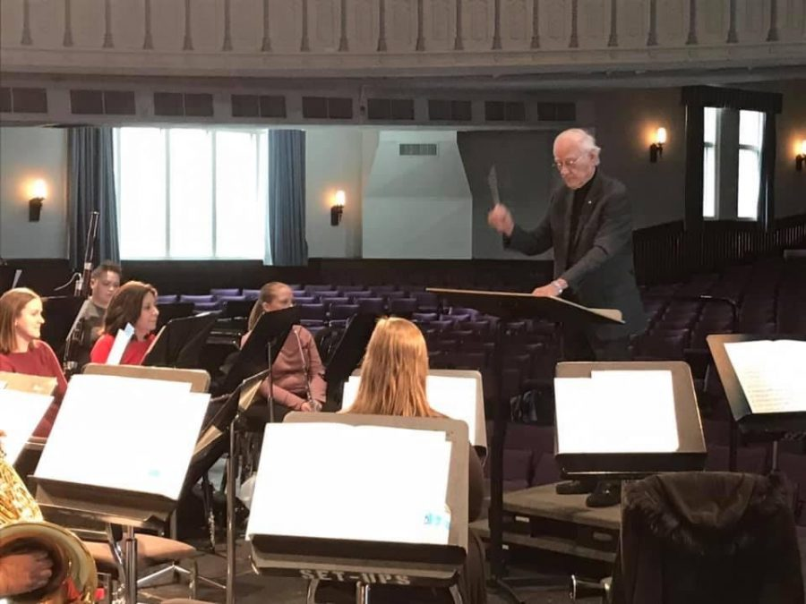 Russ Coleman, who has been the director of bands for 32 years, is conducting in front of the Alumni Band members.