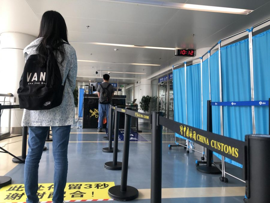 Passengers provide Chinese customs officials with their entry documents to review. Due to the COVID-19 pandemic, the process for entering China is very cumbersome.