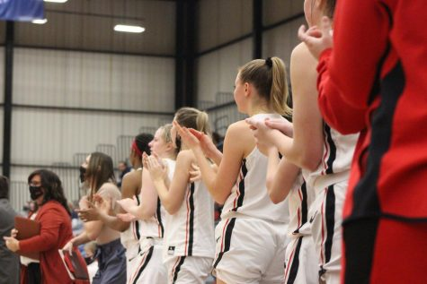 The team cheers on their teammates from the sidelines. Photo by Emily Dickmeier
