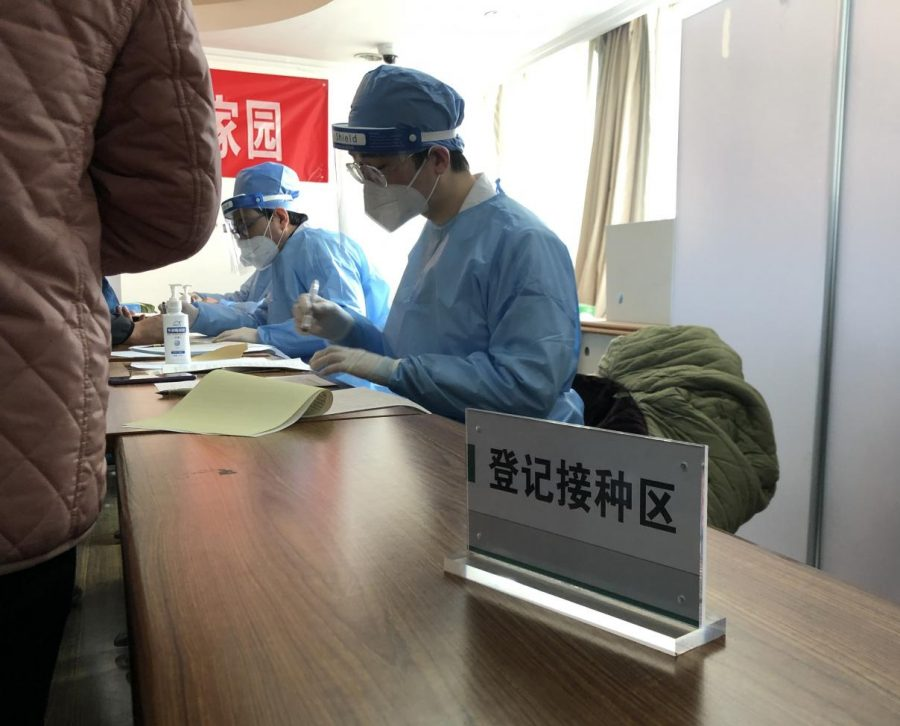 """Community medical staff are checking the information for those who are getting  vaccinated. This sign reads, """"vaccinator information registration area."""" Those who are willing to be vaccinated need to fill out the necessary information in this area and sign the consent form."""