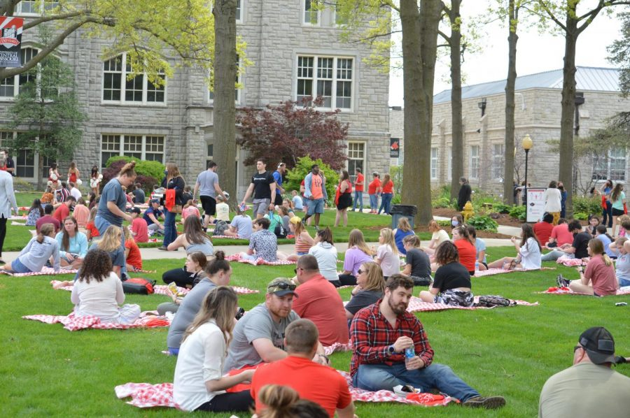Students enjoy the warm, spring weather on the provided picnic blankets while waiting for the program to begin.