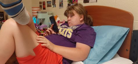 Hailey is a freshman THRIVE student who lives in Ellis. She has a roommate, and they both like anime. She is in this photo watching a YouTube video on her phone.