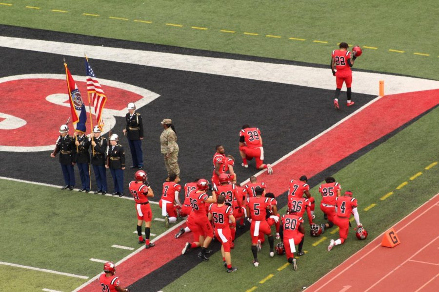 Before the first football game starts, some Mules players pray for the game.