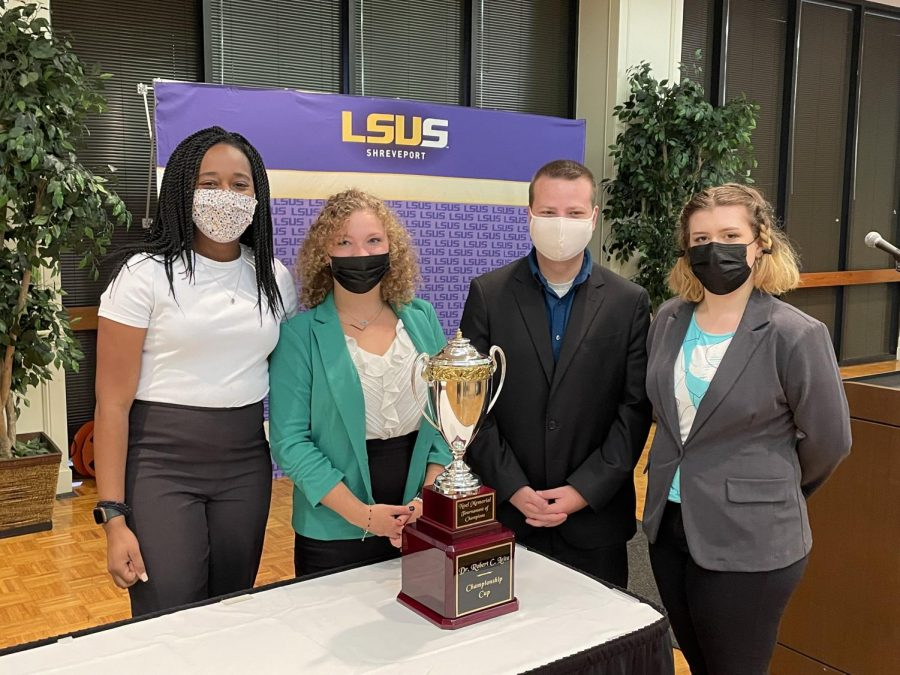 Talking Mules Speech and Debate and the Mock Trial teams joined together to form a super academic team. Here they stand next to the Noel Cup. From left to right: Chrisha Smith, Lillian Rhodes, Scott Hasek, Ryann Hill. Photo submitted by Stephanie Rogers